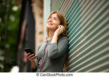 young woman leaning against wall listening to music with mobile phone and earphones