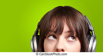 portrait of young woman listening to music over green