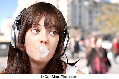 portrait of young woman listening to music with bubble gum at crowded street