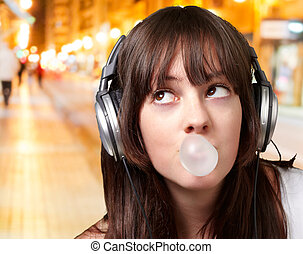 portrait of young woman listening to music with bubble gum at night city