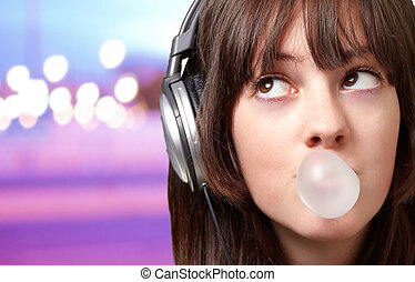 portrait of young woman listening to music with bubble gum over abstract lights