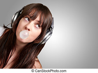 portrait of young woman listening to music with bubble gum over grey background
