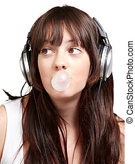 portrait of young woman listening to music with bubble gum over white