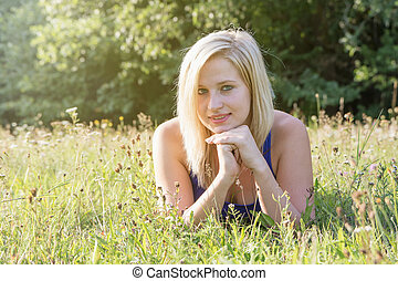 Portrait of young woman lying in the grass