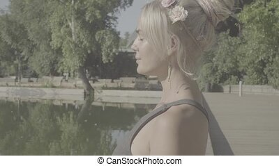 Portrait of young woman meditating near the lake