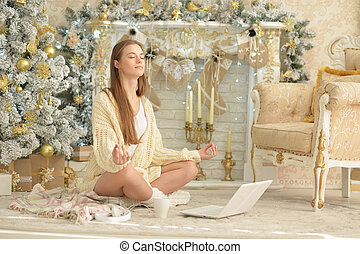 Portrait of young woman meditating while sitting near Christmas tree