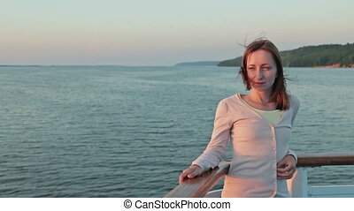 Portrait of young woman on cruise ship at sunset.