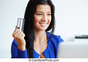 Portrait of young woman paying with a credit card