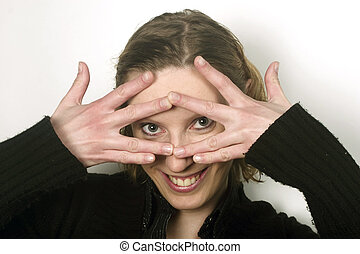 Portrait of young woman peeking thorough fingers