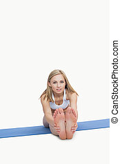 Portrait of young woman performing stretching exercise on yoga mat over white background