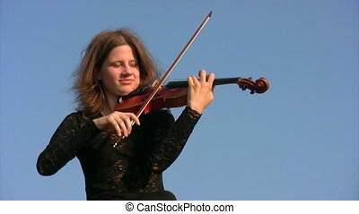 young woman plays violin against blue sky