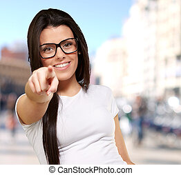 portrait of young woman pointing with finger at city