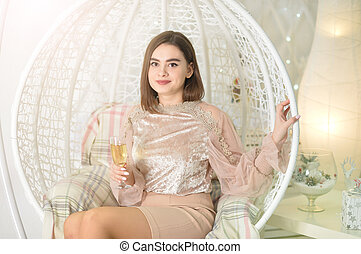 Portrait of young woman posing on swing with champagne