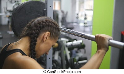 Portrait of young woman prepares to lift heavy barbells at the gym. Female athlete taking a barbell with heavy weights on her shoulders. Slow motion