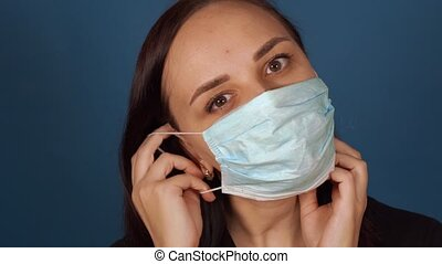 Portrait of young woman putting on medical mask on her face...
