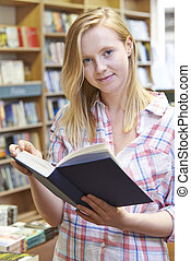 Portrait Of Young Woman Reading Book In Bookstore