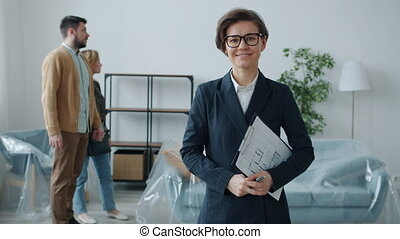 Portrait of young woman in suit realtor looking at camera standing with papers while couple choosing house talking watching interior in background