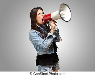 portrait of young woman screaming with megaphone against a...