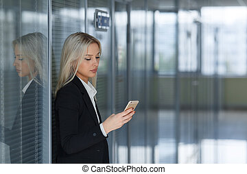 Portrait of young woman sending message on smartphone in office. Copy space