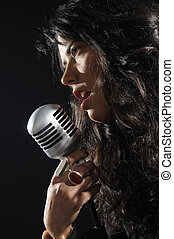 Portrait of young woman singing with retro mic