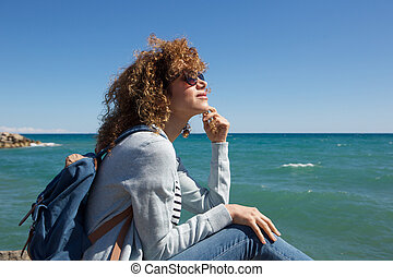 young woman sitting by seaside thinking