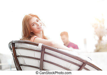 portrait of young woman sitting in a large comfortable chair.