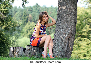 Portrait of young woman sitting in a summer park