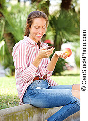 young woman sitting in park eating an apple and sending text message on mobile phone