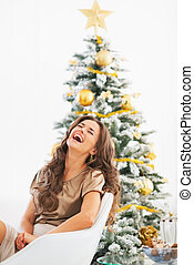 Portrait of young woman sitting near christmas tree and laughing