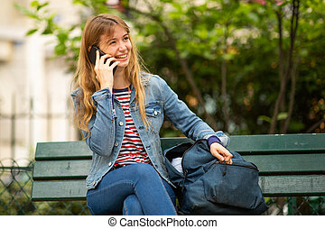 young woman sitting on park bench talking with cellphone