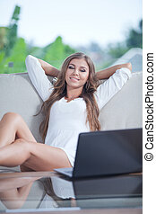 portrait of young woman sitting on sofa with laptop in summer house environment