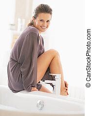 Portrait of young woman sitting on bathtub