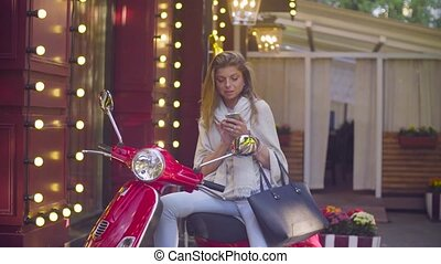 Portrait of young woman sitting on the scooter