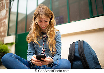 young woman sitting outside looking at cellphone