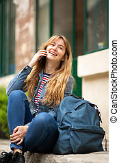 young woman sitting outside talking with cellphone