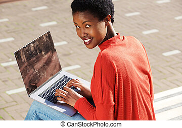 young woman sitting outside with laptop