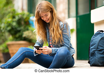 young woman sitting outside with mobile phone