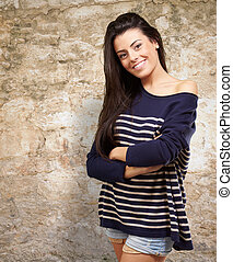 portrait of young woman smiling against a stone wall
