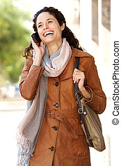 young woman smiling and talking on cellphone in the city