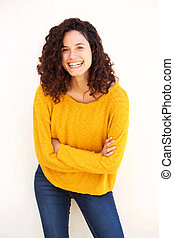 young woman smiling with arms crossed against isolated white background