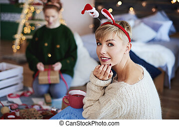 Portrait of young woman spending christmas time in bedroom