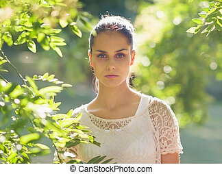 Portrait of young woman standing in foliage