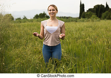 Portrait of cheerful young woman standing in green wheat field