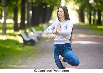 Portrait of young woman standing in yoga tree pose