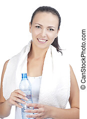 portrait of young woman standing with bottle of pure water having towel around neck isolated over white