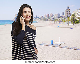 portrait of young woman talking on mobile against a beach