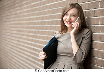 Portrait of young woman talking on phone and looking at camera on the street