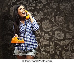 portrait of young woman talking on vintage telephone against a vintage wall