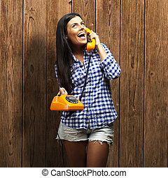 portrait of young woman talking on vintage telephone against a wooden wall