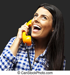 portrait of young woman talking on vintage telephone over black